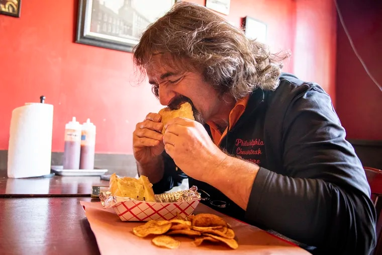 Jim Pappas, 56, of North Wilmington, Del., takes his first bite of the brisket cheesesteak from Mike's BBQ, marking his 500th cheesesteak on Wednesday, Jan. 8, 2020.