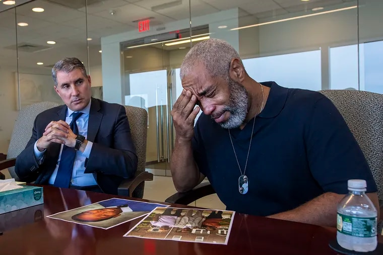 Rodney Hargrove (right) gets emotional next to his attorney, Gregory S. Spizer, during an interview with The Inquirer on Wednesday. Rodney's 20-year-old son, Rodney, was gunned down in the middle of the night in March as he waited for a ride outside the city jail after making bail.