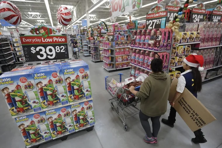 A shopper walks with a store associate in the toy section at Walmart in Teterboro, N.J The National Retail Federation said the Republican tax bill that's before the U.S. Senate for a vote on Friday would help both large and small retailers.