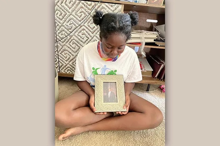 Nissah Coverdale, 11, of West Chester, holds one of her favorite photographs of her grandfather, who died of dementia and COVID-19 in May 2020.