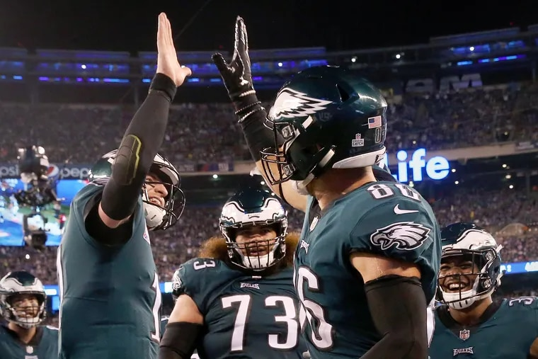 Eagles quarterback Carson Wentz (11) high-fives tight end Zach Ertz (86) after Ertz scored a touchdown in the second quarter of a game against the New York Giants at MetLife Stadium in East Rutherford, N.J., on Thursday, Oct. 11.