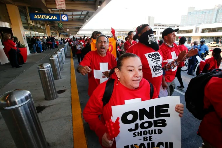 Workers with union UNITE HERE march in front of Terminal B and C at the Philadelphia International Airport during a protest against high health care costs on Thursday, Oct. 24, 2019. UNITE HERE is trying to put pressure on American Airlines, even though the union is negotiating with an American Airlines contractor, because the company is the one that holds the economic power.