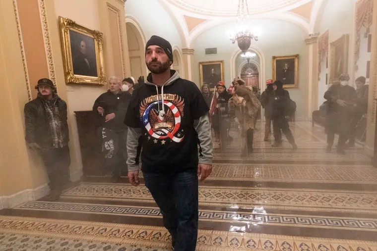 Smoke fills the walkway outside the Senate Chamber as supporters of President Donald Trump are confronted by U.S. Capitol Police officers inside the Capitol.
