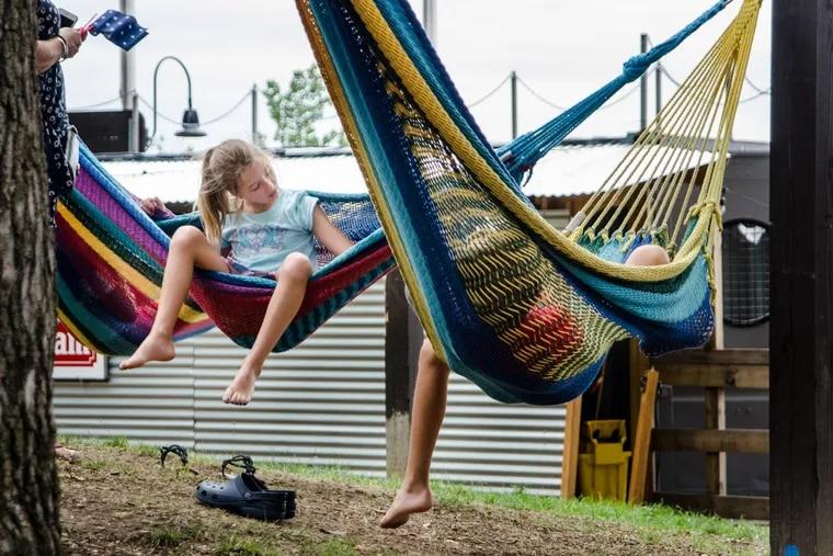 Skylar and Jonathan Schatz play in hammocks in Spruce Street Harbor Park.