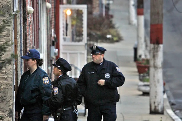 Philadelphia police investigate an alleged homicide on Collom Street in the Germantown section of Philadelphia on Monday morning.