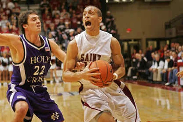 St. Joseph's Garrett Williamson drives past Holy Cross' Andrew Beinert. Williamson finishedwith seven points as the Hawks made it two wins in a row to start the season.