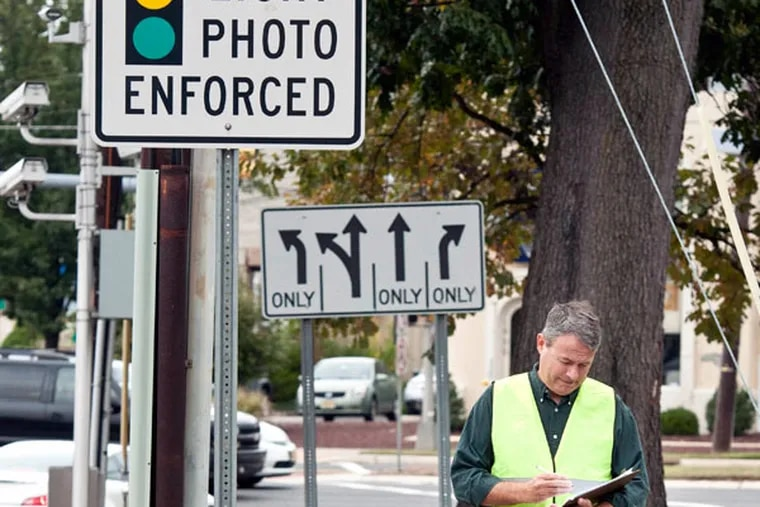 Rick Scott, a Cherry Hill father of four who's on a crusade against red light cameras, keeps track of the camera at the corner of Springdale and Route 70 in Cherry Hill. ( RON TARVER / Staff Photographer ) October 2, 2014