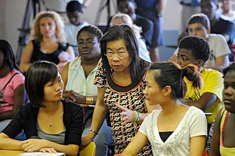 New students Mandy Huang (left) and her sister Mei Hui Huang, who came to the United States six months ago, listen to translator Vam Tsang during the new-student assembly at South Philadelphia High School. (CLEM MURRAY / Staff Photographer)