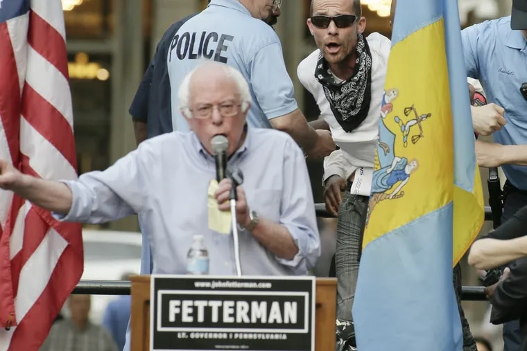 An unidentified man leaps onto the stage as Bernie Sanders speaks during a John Fetterman for lieutenant governor rally at Phila. City Hall in Phila., Pa. on May 4, 2018.
