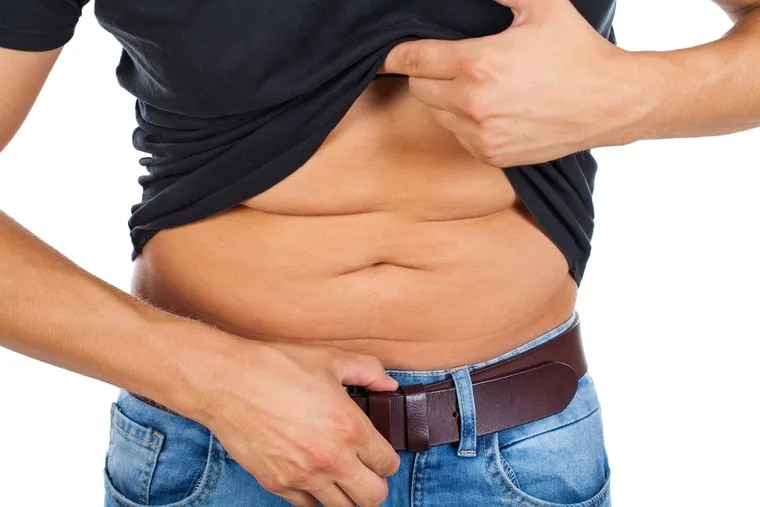 Close up picture of a caucasian young man's fatty abdomen on isolated background