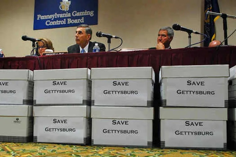 Piles of petitions against the proposed Gettysburg casino line a table as the Gaming Control Board hears testimony.