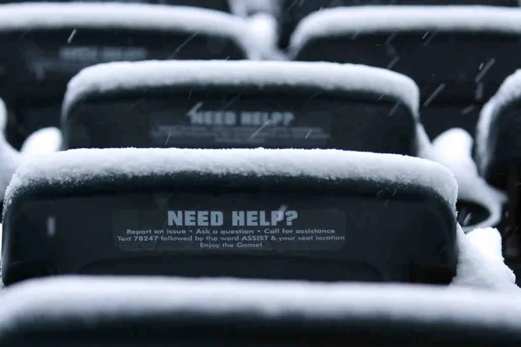 """Snow falls on Lincoln Financial Field seats with """"need help"""" signs."""