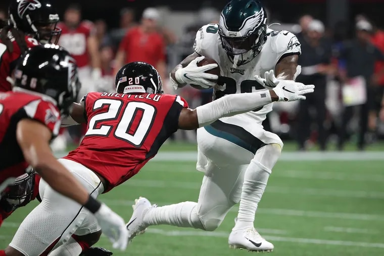 Eagles running back Miles Sanders tries to break a tackle by Atlanta Falcons defensive back Kendall Sheffield, left, in the 2nd quarter as the Philadelphia Eagles play the Atlanta Falcons in Atlanta, GA on September 15, 2019. .