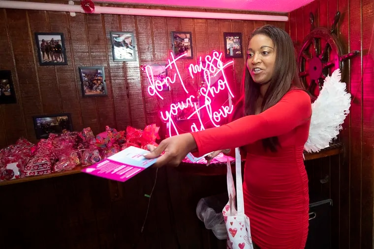 """Nia Ferguson portrays Cupid as part of a """"Shot at Love"""" campaign in the downtown areas of Montgomery County, handing out swag and vaccination information on Thursday night at Flanigan's Boathouse in Conshohocken.  """"A lot of people have been saying that they're already vaccinated, which is good,"""" Ferguson said, adding of her costume, """"People love the wings, too."""""""