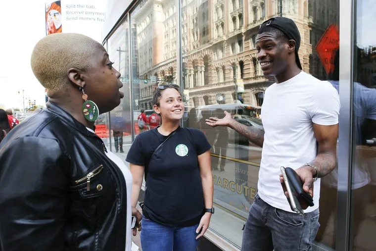 Starbucks worker Jordan Crockett (right) talks about the coffee company's racial-bias training with Ashley Pasquarella (center) and Jaicee Huff during a break outside the Loews Hotel on Tuesday.
