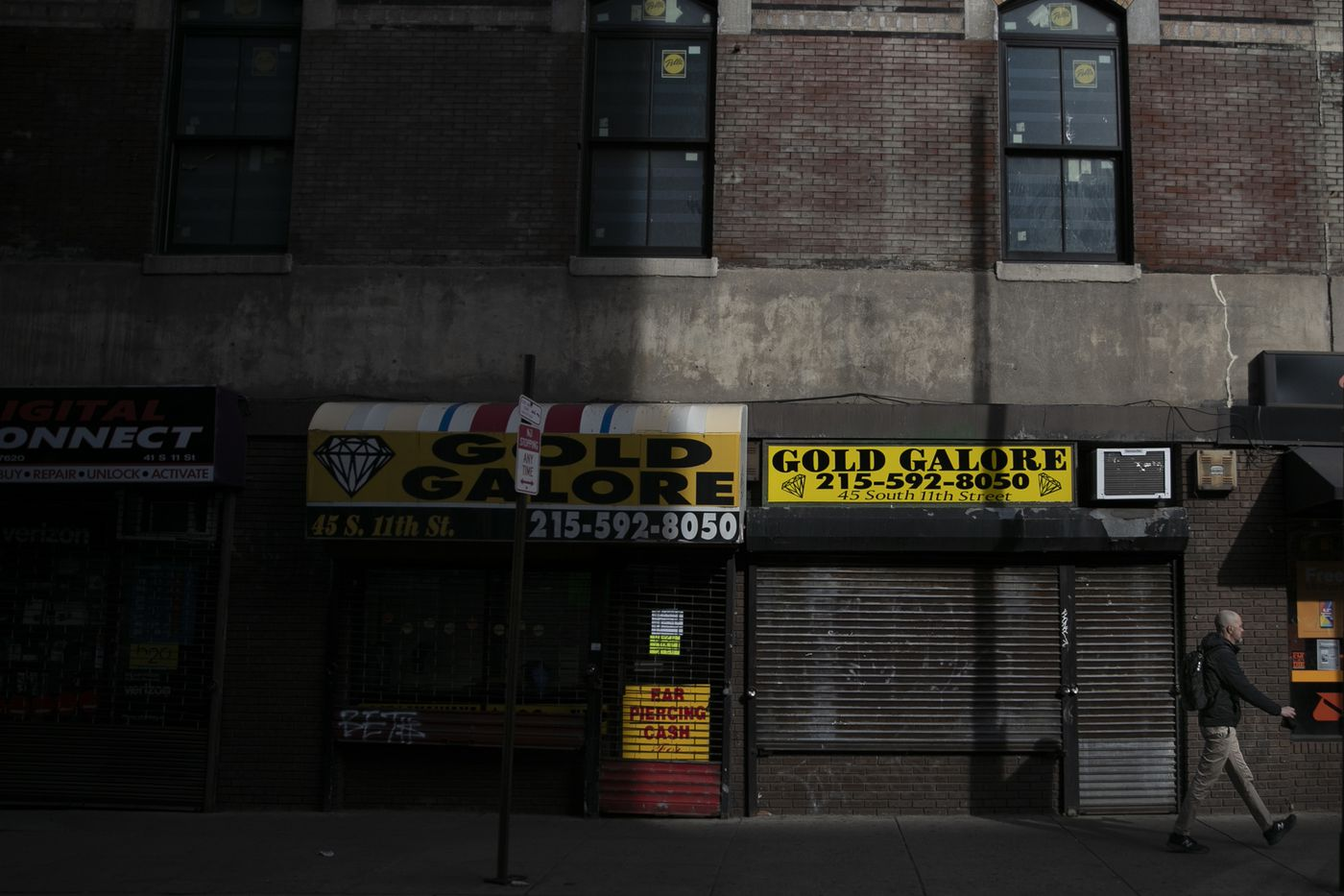Shuttered businesses are seen along 11th street towards Chestnut street in Center City on Tuesday, March 24, 2020. Non-essential businesses are closed and a stay-at-home order has been issued by the city, with the exception of those working for life-sustaining businesses, due to the spread of the coronavirus.