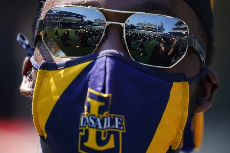Lincoln Financial Field is reflected in sunglasses worn by Samir Inge, who was receiving his MBA, as he waits to walk onto the stage during La Salle University's Class of 2021 commencement at the stadium in South Philadelphia on Saturday, May 15, 2021. Approximately 1,500 students graduated from the university Saturday in the first such ceremony to be held in the stadium.
