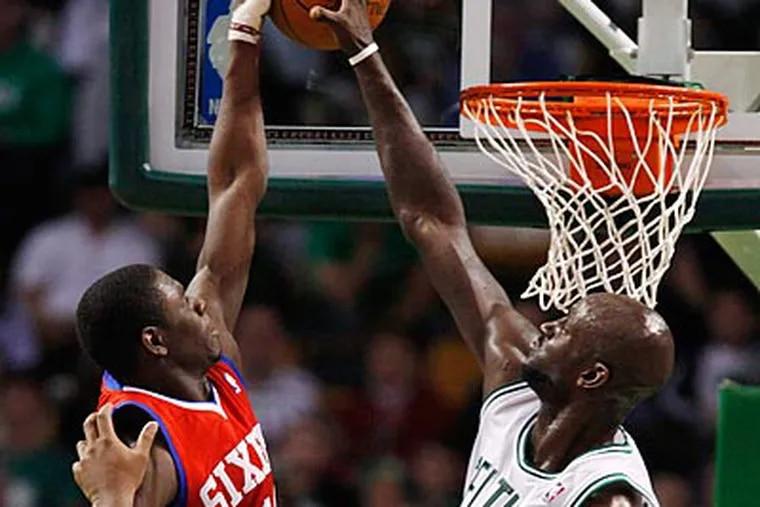 Kevin Garnett blocks Jrue Holiday's shot in the first quarter. (Michael Dwyer/AP)