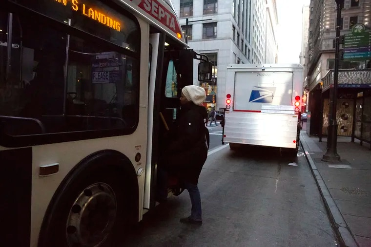 Pedestrians board a Route 21 SEPTA bus in the middle of Chestnut Street and Broad due to a postal delivery truck in the bus lane during rush hour. Congestion is an increasing problem in Center City.