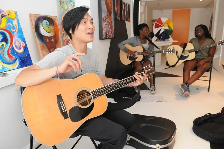 """Christian """"Sap"""" Tizon teaching his students how to handle the guitar in a free music class at Urban Art Gallery 262 S. 52nd Street Philadelphia Pa June 16, 2018"""