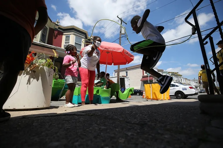 Adrianna Carter (left), a neighbor, turns a jump rope for Shyion Charles, 9, during a Play Streets event on the 200 block of South Alden Street in West Philadelphia.