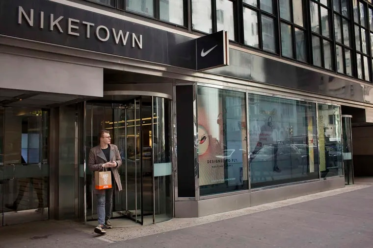 A shopper exits a Niketown store in New York City. Nike Inc., the world's largest sporting-goods maker, posted third-quarter profit that topped analysts' estimates, helped by demand for athletic footwear in North America. Net income in the quarter ended Feb. 28 rose 16 percent to $791 million, or 89 cents a share, from $682 million, or 75 cents, a year earlier, the Beaverton, Ore.-based company said Thursday in a statement.
