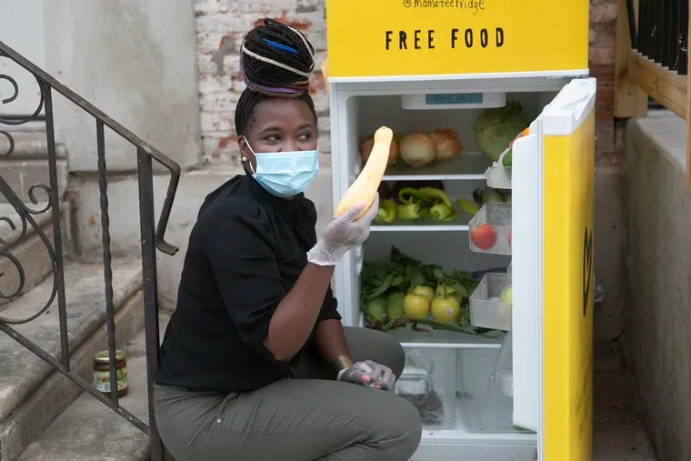 Michelle Nelson, founder of Mama-Tee, shows off a squash that was donated while she restocks the Community Fridge outside of Ambassador restaurant in the Ludlow neighborhood of Philadelphia on Saturday.
