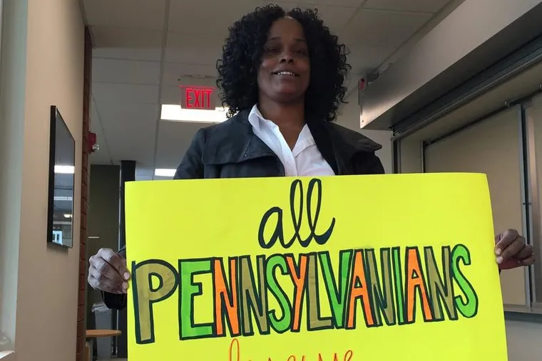 """Tawanda Preston, a patient navigator at a Drexel University infectious diseases clinic, holds a sign saying """"All Pennsylvanians Deserve Access"""" during a state advisory committee discussion  in Mechanicsburg, Pa., last year."""