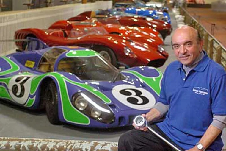 """Dr. Fred Simeone by a row of antique race cars in a simulated """"pit row"""" of the world-famous 24 Hours of LeMans race in the soon-to-be open Simeone Foundation Museum. (Clem Murray / Inquirer)"""