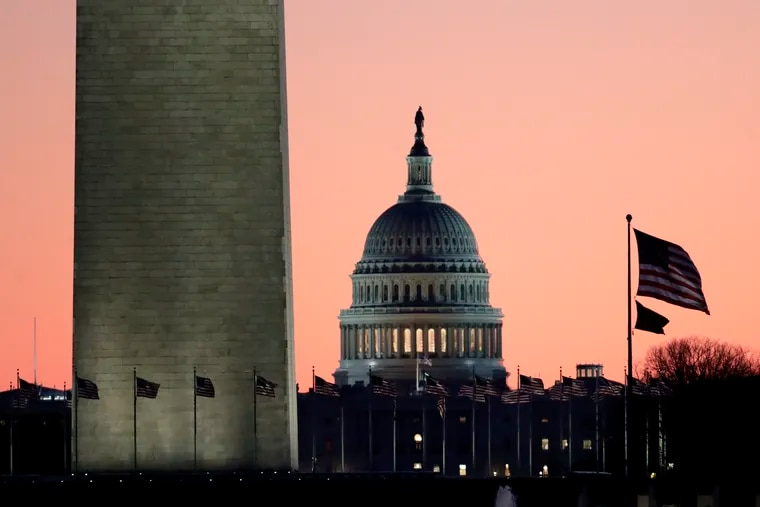 The U.S. Capitol building, center, is seen next to the bottom part of the Washington Monument, left, before sunrise on Capitol Hill in Washington, Thursday, Dec. 19, 2019.