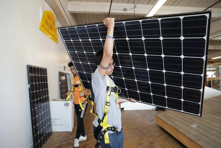 The ECA, in partnership with the Philadelphia Energy Authority, created a solar installation training program for high schoolers. William Gonzalez, 16, practices carrying a solar panel on a simulated roof at the training center in Philadelphia, PA on July 24, 2019.