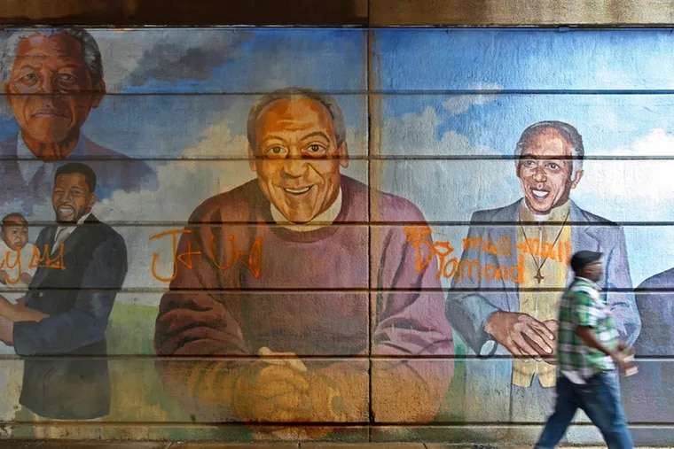 A portrait of Bill Cosby stares out at passersby as they walk under the bridge at North Broad Street near Indiana. The city's Mural Arts Program plans to remove a mural. ( Michael Bryant / Staff Photographer )