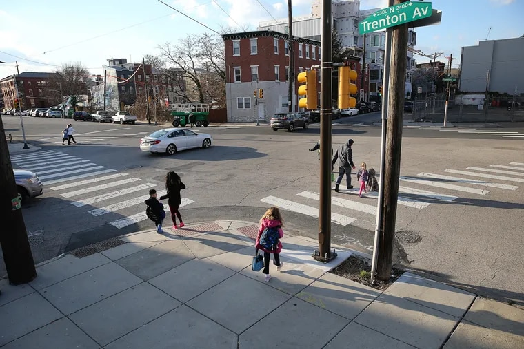 Pedestrians make their way across the complicated, five-way intersection of Frankford Avenue, Trenton Avenue and York Street after school let out in the East Kensington section of Philadelphia.  The city plans to install a traffic circle at the location.