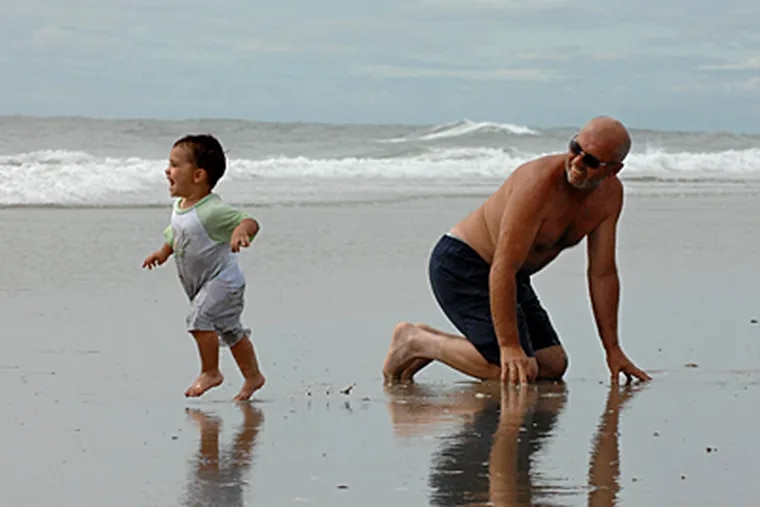 Dominic Polidoro from Wenonah, and grandfather, Wallace Whittaker, enjoy the surf in North Wildwood. (Inquirer file photo)