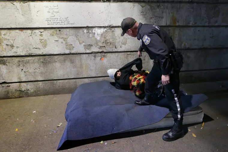 A Philadelphia police officer wakes up a homeless man as workers perform a weekly cleanup under a Kensington bridge. Workers had called police to wake the man up. After several attempts, the man got up.