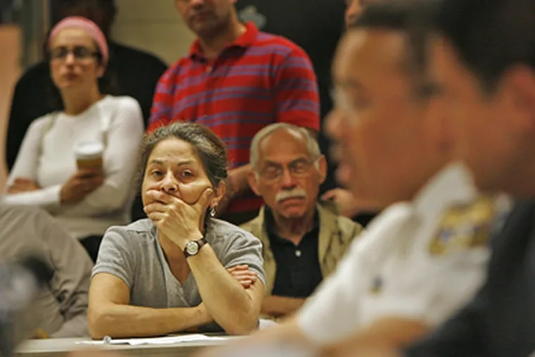 A South Street area resident listens to police officials during a community meeting at the Palumbo Recreation Center today. (Alejandro A. Alvarez / Staff Photographer)
