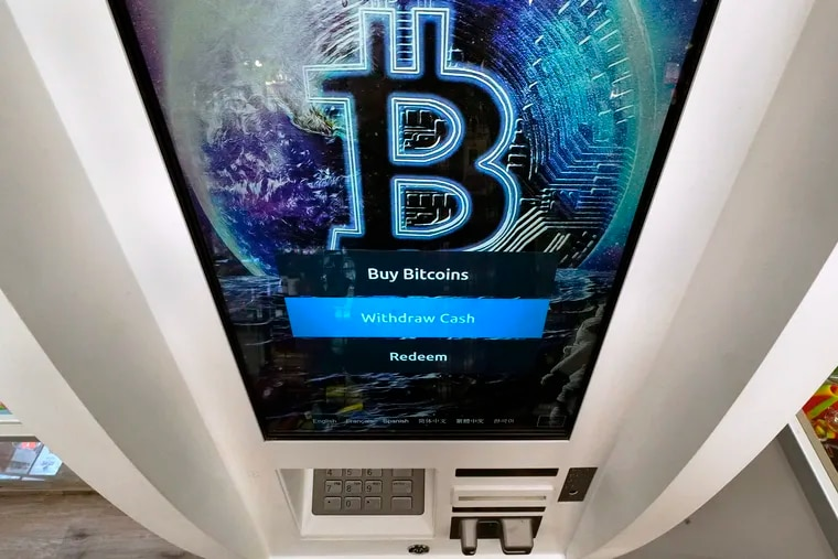 The Bitcoin logo appears on the display screen of a crypto currency ATM at the Smoker's Choice store, Tuesday, Feb. 9, 2021, in Salem, N.H.  After a wild week in which Bitcoin soared to new heights, Bitcoin is crossing the $54,000 mark. Bitcoin rallied last week as more companies signaled the volatile digital currency could eventually gain widespread acceptance as a means of payment for goods and services. (AP Photo/Charles Krupa)