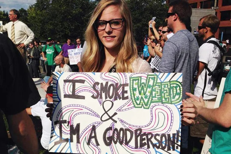 A PhillyNORML volunteer holds a sign at a Smoke Down Prohibition rally in Philadelphia's Independence National Historic Park