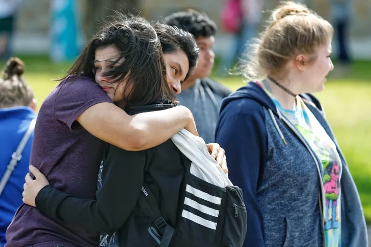 Following the May shooting at Santa Fe High School in Texas, freshman Caitlyn Girouard (center) hugged a friend as students and parents waited to reunited.