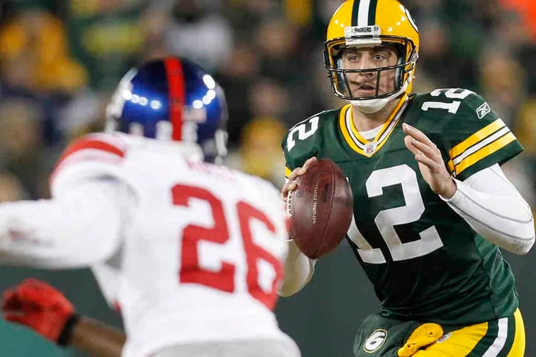 Packers quarterback Aaron Rodgers, back from a concussion, looks to pass in front of Antrel Rolle.