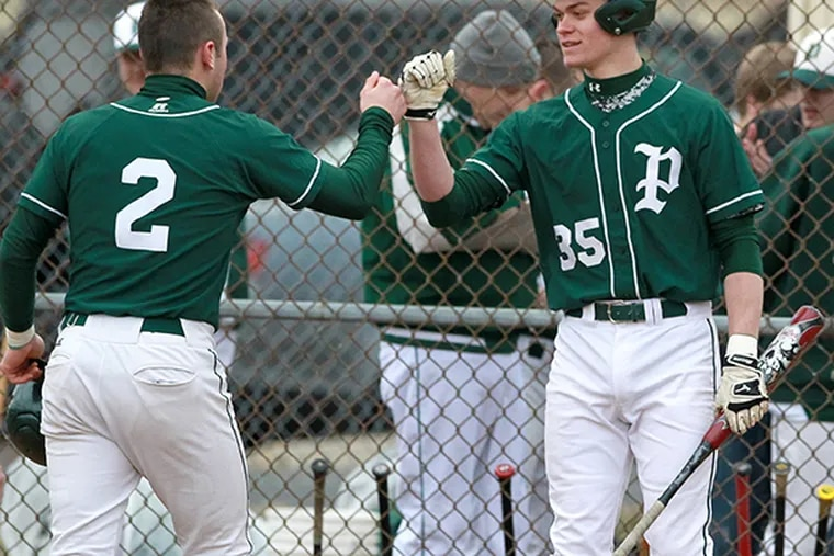 Dan Long, left, of Pennridge is congratulated by teammate Tommy Nuneviller, right, after he scored on a hit by David Tatoian in the 4th inning against Central Bucks East  in a Suburban One League baseball game on March 30, 2015. (Charles Fox/Staff Photographer)