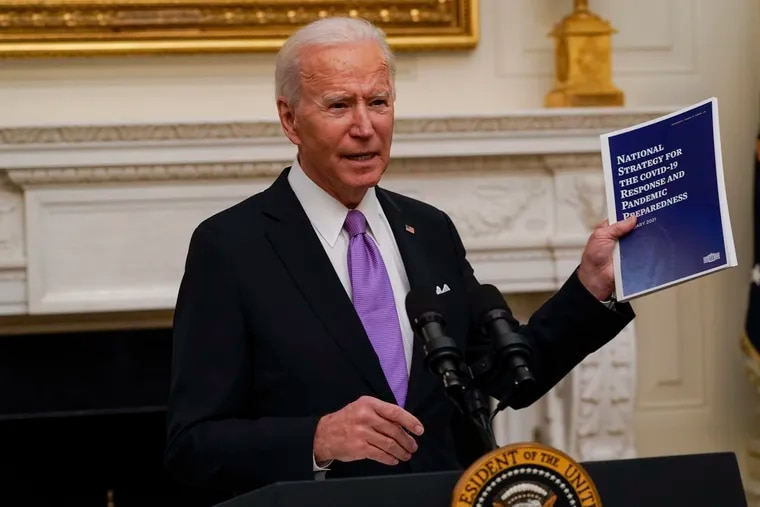 President Joe Biden holds up a copy of his coronavirus pandemic response plan at a news conference in the White House.