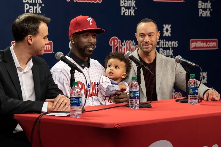 Andrew McCutchen, center, balances his 1-year-old son, Steel, on his knee during an introductory press conference Tuesday at Citizens Bank Park.