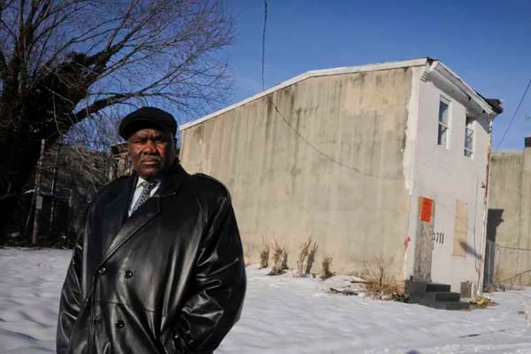 """Rev. Harry Moore, pastor of Mount Olive Baptist Church, stands beside a house at 3711 Melon St., in Mantua where he will preside over a """"funeral"""" for the house in an attempt to recognize Mantua's past, embrace its present and celebrate its potential rebirth with the help of a federal Promise Zone. ( RON TARVER / Staff Photographer ) February 17, 2014"""