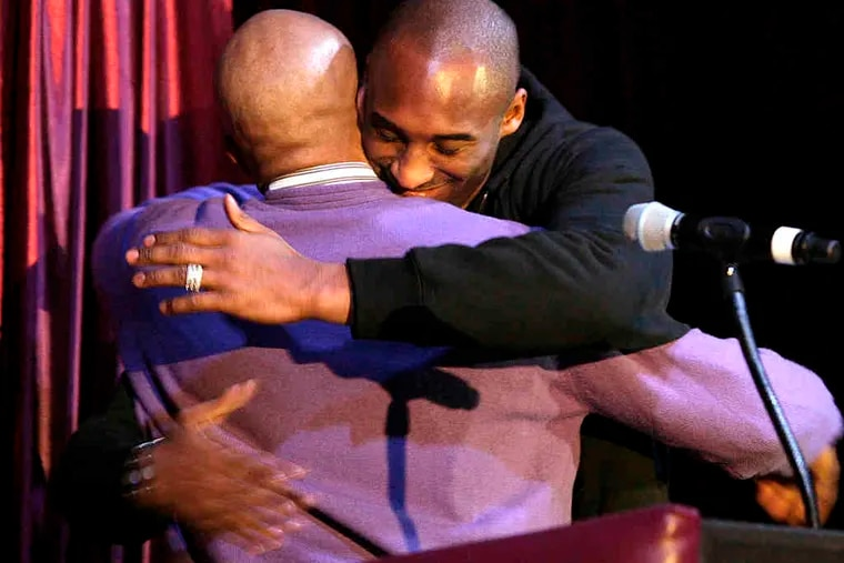 The Lakers' Kobe Bryant hugs teammate Derek Fisher during dedication ceremonies at a new Lower Merion High gymnasium that now bears his name. Bryant led the Aces to the 1996 state championship before turning pro a few months later. Story, D6.