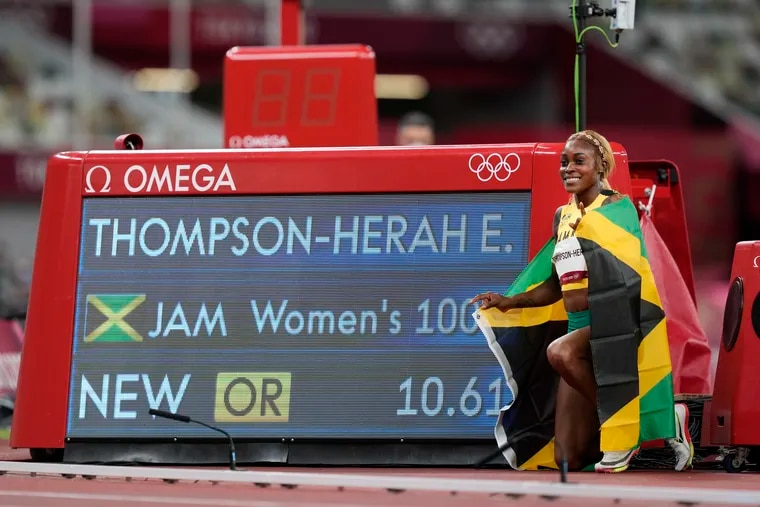 Elaine Thompson-Herah, of Jamaica, celebrates by the video board showing her new Olympic record time in the women's 100-meter final.