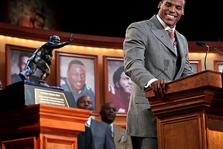 Auburn's Cam Newton looks at the trophy while he makes his acceptance speech. (AP Photo/Heisman Trophy Trust, Kelly Kline)