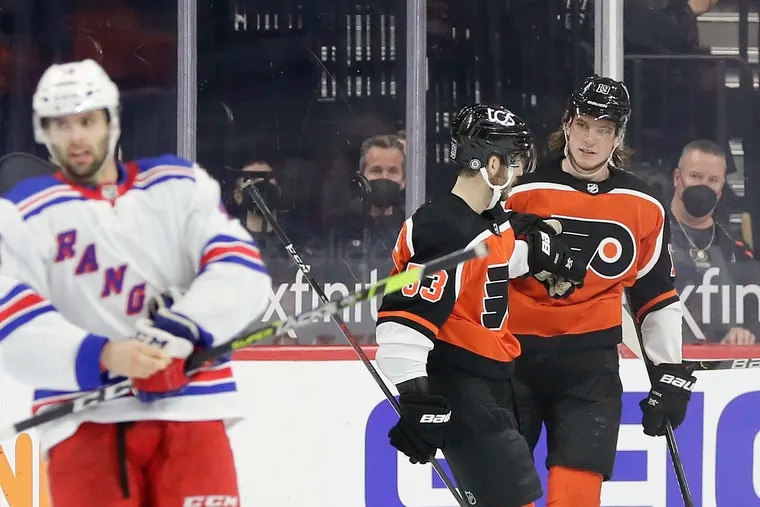 Flyers center Nolan Patrick (right) celebrates his second-period power play goal with Shayne Gostisbehere as New York Rangers center Colin Blackwell skates away on Saturday. The Flyers rallied for a 2-1 win.