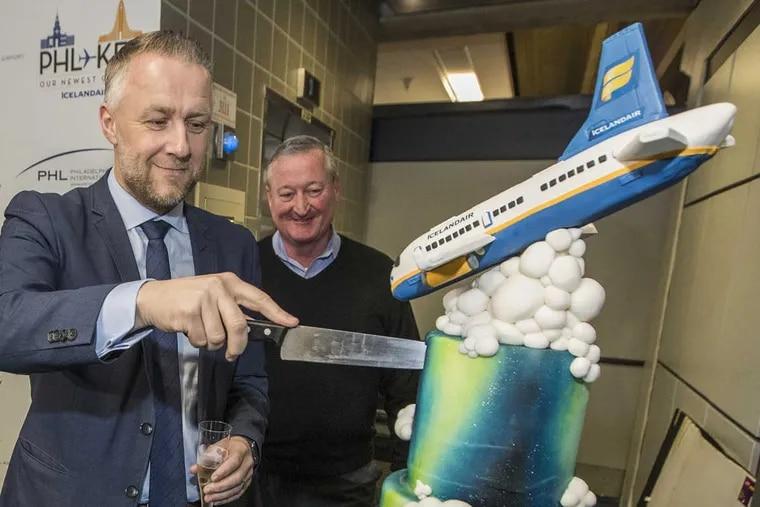 Icelandair CEO Birkir Holm Guonason, left, cuts a cake to celebrate Icelandair's inaugural flight to Philadelphia as Mayor Philadelphia James Kenney, right, look on.