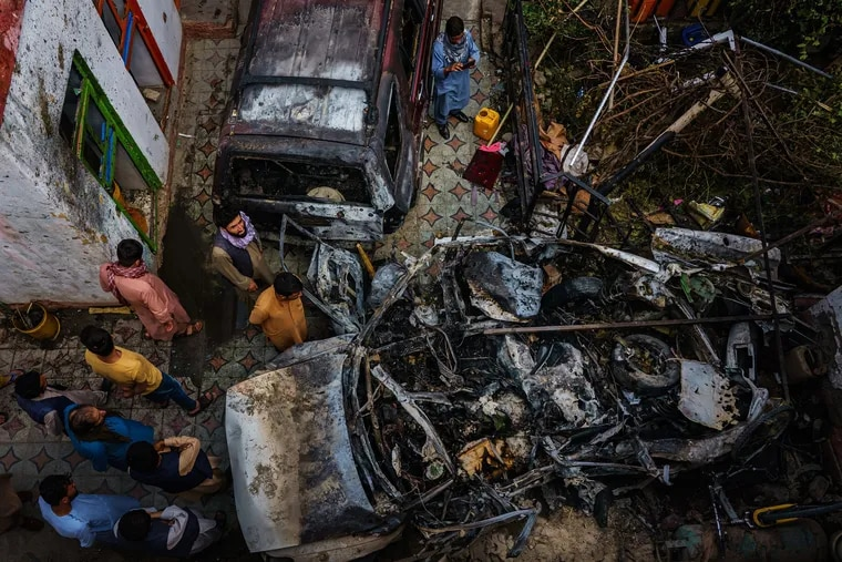 Relatives and neighbors of the Ahmadi family gathered around the incinerated husk of a vehicle that the family says was hit by a U.S. drone strike, killing 10 people, in Kabul, Afghanistan, Aug. 30.